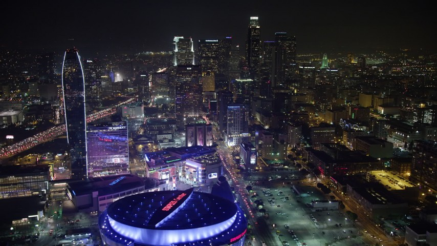 5K aerial video fly over Staples Center toward Downtown Los Angeles skyscrapers, California, night Aerial Stock Footage AX64_0363