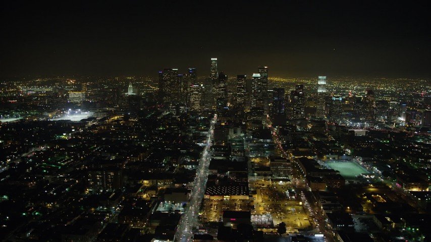 5K aerial video follow 6th Street to approach Downtown Los Angeles and skyscrapers, California, night Aerial Stock Footage | AX64_0379