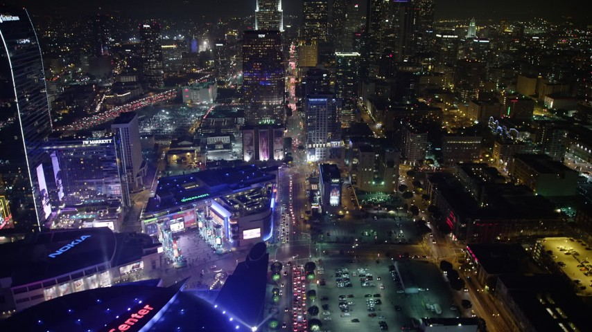 5K stock footage aerial video tilt from Staples Center arena to reveal skyscrapers in Downtown Los Angeles, California, night Aerial Stock Footage AX64_0408 | Axiom Images