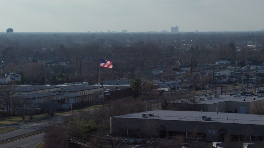 5K stock footage aerial video of an American flag flying over warehouse buildings in Farmingdale, Long Island, New York Aerial Stock Footage | AX65_0001