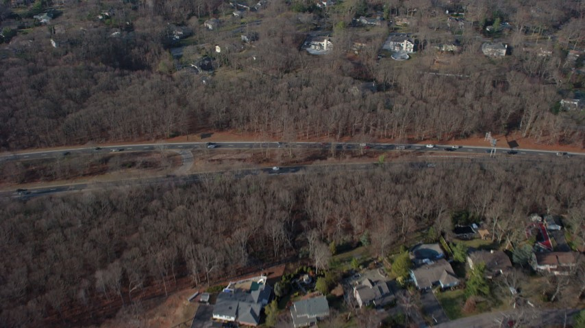 5K stock footage aerial video bird's eye view of suburban homes, leafless trees, and highway in Plainview, Long Island, New York, winter Aerial Stock Footage | AX65_0008