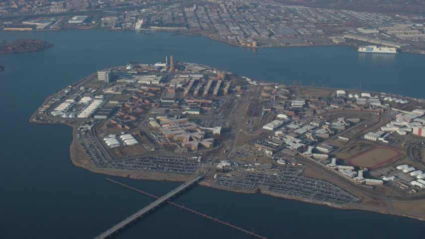 Flying by Rikers Island prison in New York City, winter Aerial Stock Footage AX65_0039