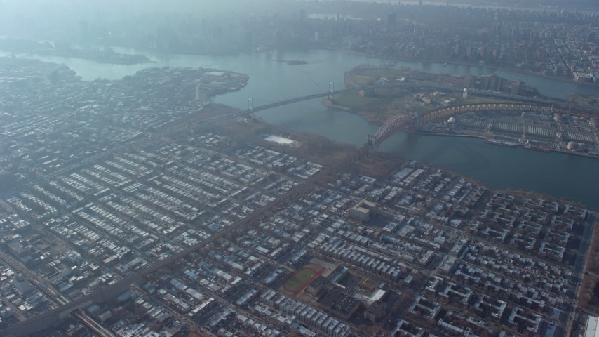 5K stock footage aerial video fly over urban neighborhoods to approach Astoria Park and bridges spanning the East River in Queens, New York City, winter Aerial Stock Footage | AX65_0041