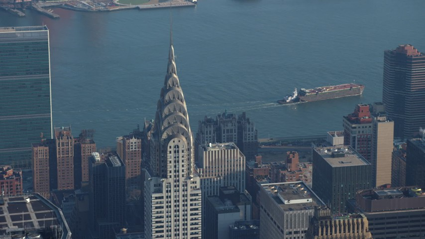 5K stock footage aerial video track the top of the Chrysler Building, United Nations in the background, Midtown Manhattan, New York City, winter Aerial Stock Footage | AX65_0062