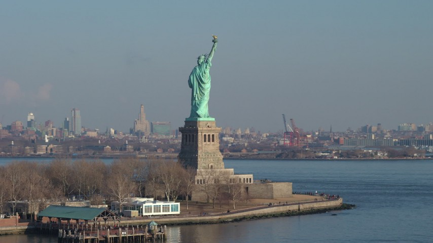 5K stock footage aerial video orbit the torch side of the Statue of Liberty, New York, Brooklyn in the background, winter Aerial Stock Footage | AX65_0079