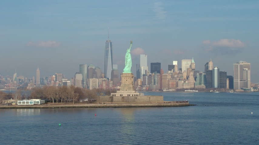 5K stock footage aerial video flyby Statue of Liberty to focus on Freedom Tower and Lower Manhattan skyline in the distance, New York City, winter Aerial Stock Footage | AX65_0082