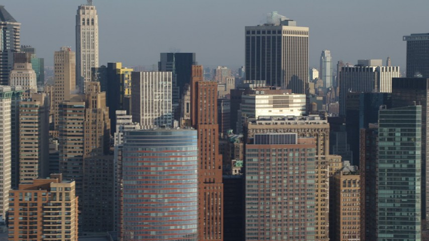 Flying by skyscrapers in Lower Manhattan, New York City, winter, revealing Brooklyn skyscrapers across the East River Aerial Stock Footage | AX65_0096