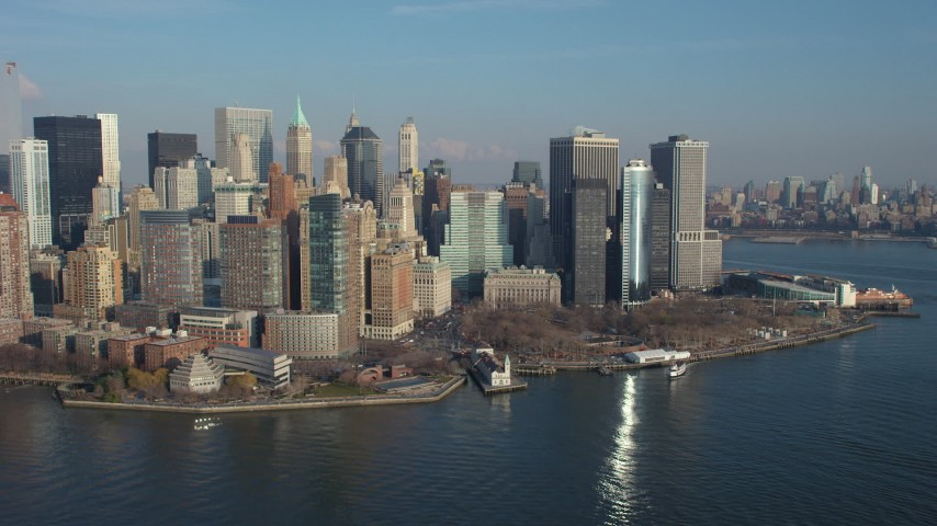 Flying by Battery Park and the Lower Manhattan skyline, New York City, winter Aerial Stock Footage | AX65_0097