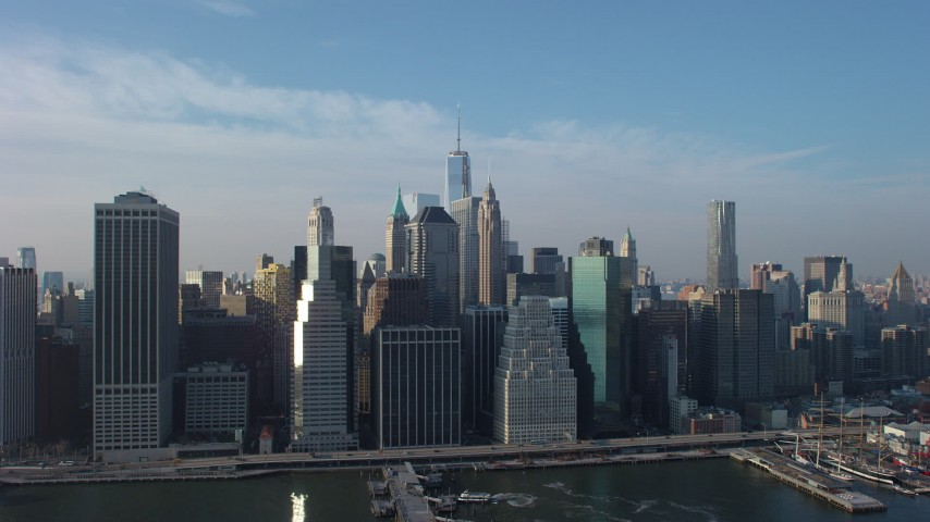 Lower Manhattan skyscrapers and East River piers, Freedom Tower in the distance, New York City, winter Aerial Stock Footage | AX65_0103