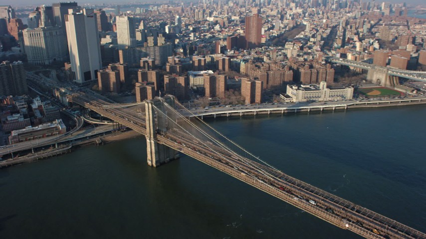 Tilt to heavy traffic crossing the Brooklyn Bridge, New York City, winter Aerial Stock Footage | AX65_0104