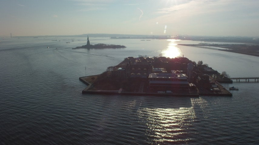 5K stock footage aerial video of Statue of Liberty behind Ellis Island in New York, winter Aerial Stock Footage | AX65_0125