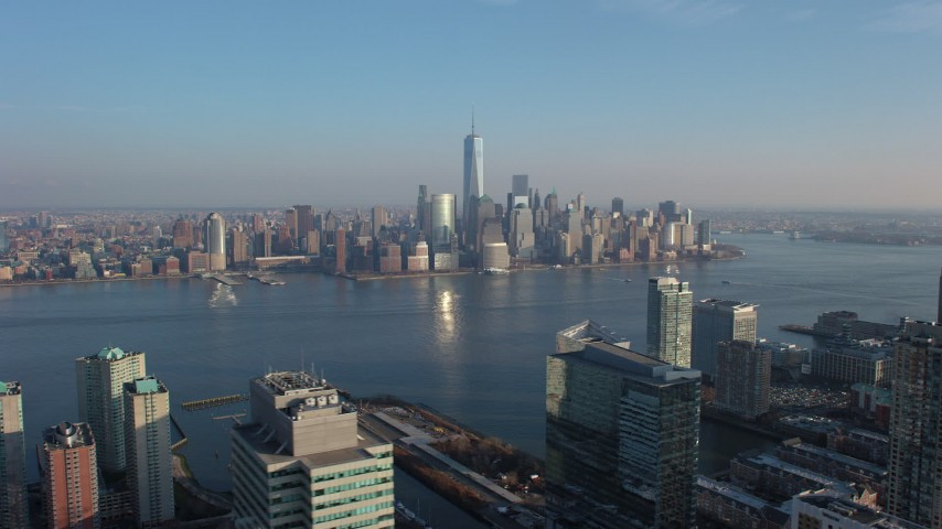 A view of the Lower Manhattan skyline seen from across the Hudson River, New York City, winter Aerial Stock Footage | AX65_0131