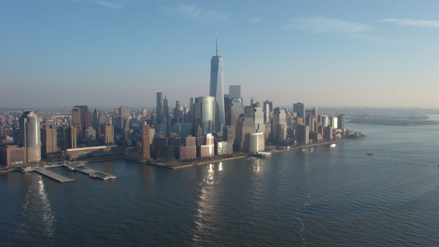 5K stock footage aerial video fly over Hudson River to approach One World Trade Center and the Lower Manhattan skyscrapers, New York City, winter Aerial Stock Footage | AX65_0134