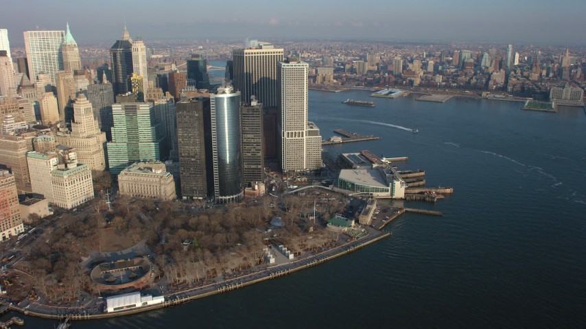 Flying by Lower Manhattan skyscrapers and Battery Park in winter, with a view down the East River, New York City, winter Aerial Stock Footage | AX65_0139