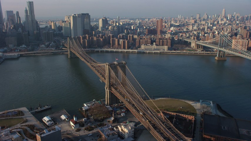 5K stock footage aerial video flyby the Brooklyn Bridge with heavy traffic and reveal the Lower Manhattan skyline, New York City, winter Aerial Stock Footage | AX65_0144