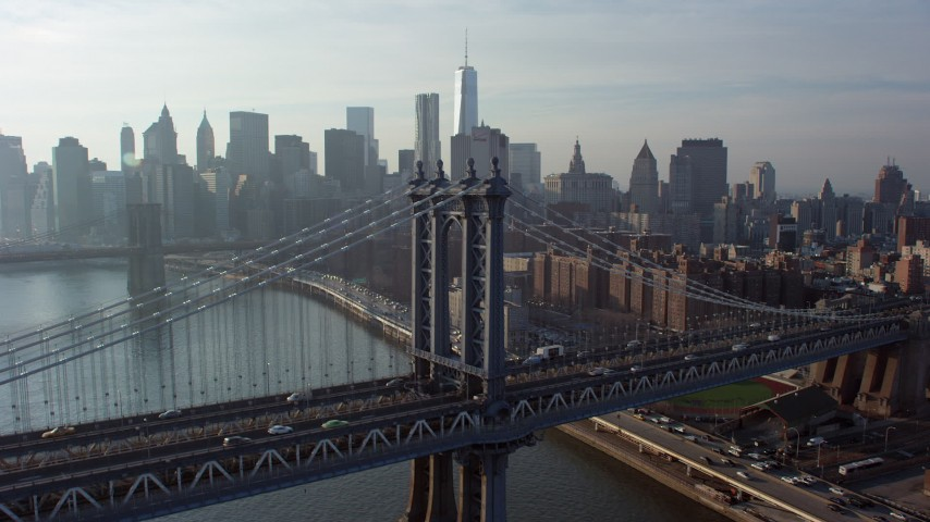 5K stock footage aerial video fly over the Manhattan Bridge to focus on the Brooklyn Bridge and the Lower Manhattan skyline, New York City, winter Aerial Stock Footage | AX65_0148