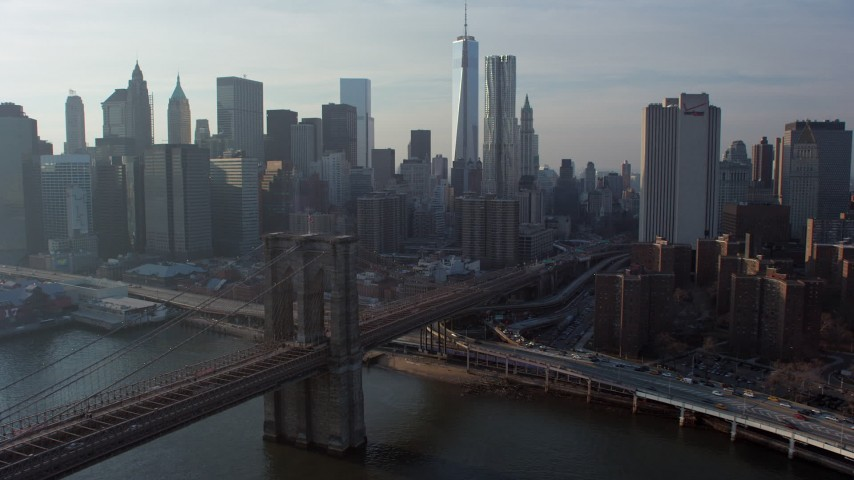 5K stock footage aerial video flyby the Brooklyn Bridge and focus on Freedom Tower and the Lower Manhattan skyline, New York City, winter Aerial Stock Footage | AX65_0150