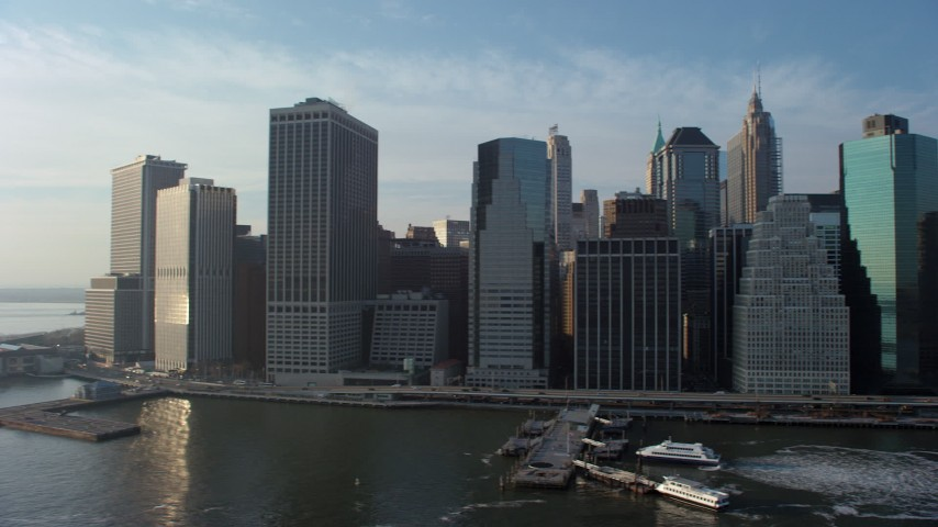 Pan across the Lower Manhattan skyline, revealing piers and historic ships, New York City, winter Aerial Stock Footage | AX65_0152