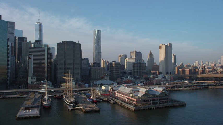 5K stock footage aerial video of historic ships docked at East River piers and the Lower Manhattan skyline, New York City, winter Aerial Stock Footage | AX65_0153