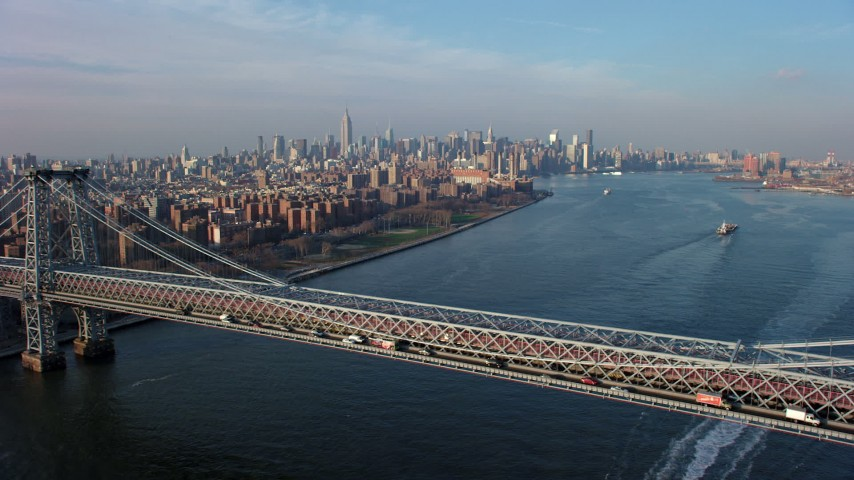 Fly over the Williamsburg Bridge toward Midtown Manhattan skyline in the background, New York City, winter Aerial Stock Footage | AX65_0158