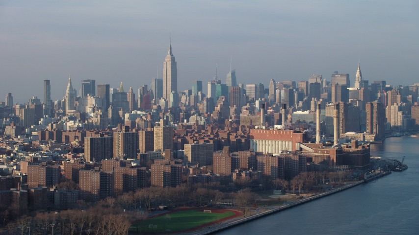 Empire State Building and Midtown Manhattan skyline seen from power plant by East River, New York City, winter Aerial Stock Footage | AX65_0159