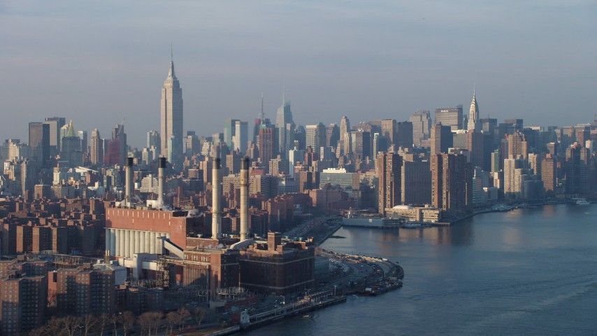 The Empire State Building and Midtown skyline seen from power plant by East River, New York City, winter Aerial Stock Footage | AX65_0160