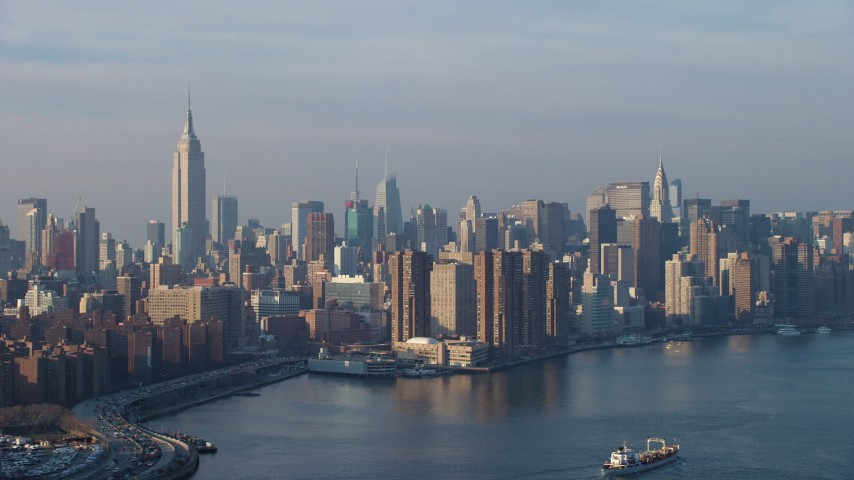 The Empire State Building and Midtown skyline seen from the East River, New York City, winter Aerial Stock Footage | AX65_0161