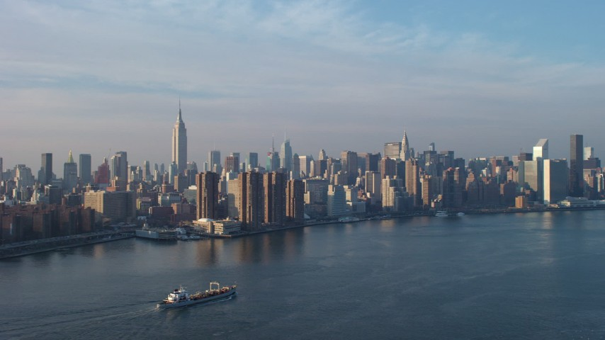5K stock footage aerial video of Empire State Building, riverfront high-rises, and Midtown skyline seen from the East River, New York City, winter Aerial Stock Footage | AX65_0162