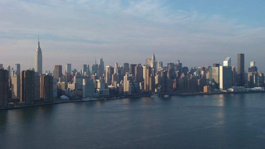 5K stock footage aerial video of riverfront high-rises, and Midtown skyline seen from the East River near the UN, New York City, winter Aerial Stock Footage | AX65_0163