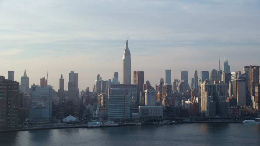 Empire State Building and riverfront condo complexes seen from the East River, Midtown Manhattan, New York City, winter Aerial Stock Footage | AX65_0164