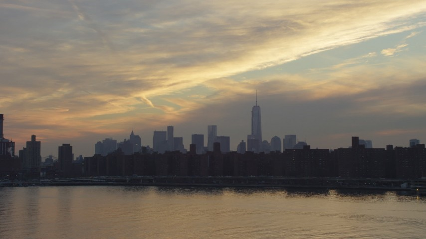Lower Manhattan skyline seen while flying low over East River by Stuyvesant Town, New York City, winter, sunset Aerial Stock Footage | AX65_0168