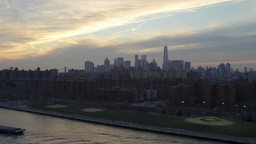 5K stock footage aerial video of Lower Manhattan skyline seen from public housing by the East River on the Lower East Side, New York City, winter, sunset Aerial Stock Footage | AX65_0171
