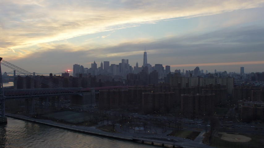 5K stock footage aerial video Lower Manhattan skyline seen from public housing on the Lower East Side and Williamsburg Bridge, NYC, winter, sunset Aerial Stock Footage | AX65_0172
