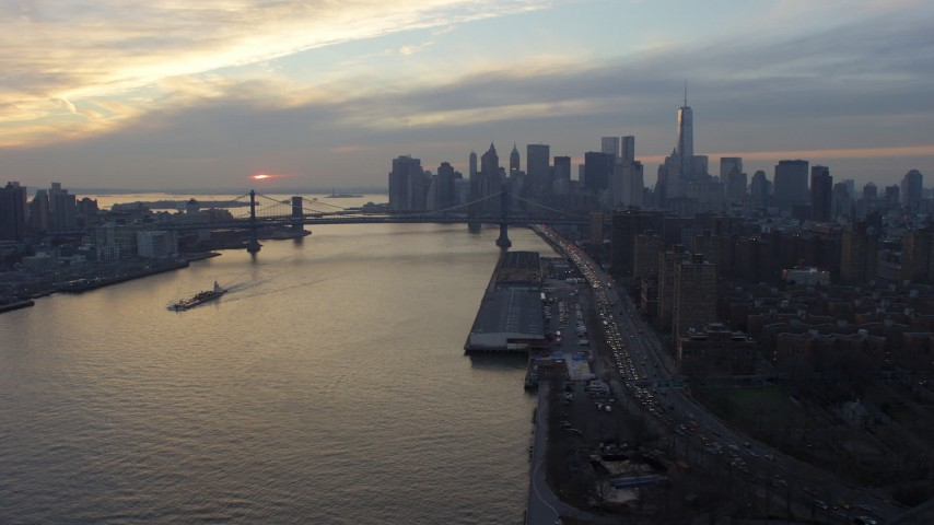 5K stock footage aerial video of Lower Manhattan skyline and Manhattan Bridge while approaching barge on the East River, NYC, winter, sunset Aerial Stock Footage | AX65_0174