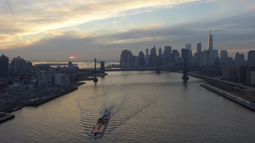 5K stock footage aerial video fly over barge on East River to approach Lower Manhattan skyline and Manhattan Bridge, New York City, winter, sunset Aerial Stock Footage | AX65_0175