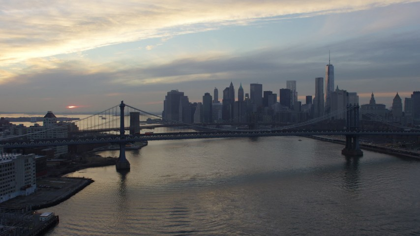 Follow East River to approach Manhattan Bridge, Brooklyn Bridge, and Lower Manhattan skyline, New York City, winter, sunset Aerial Stock Footage AX65_0176