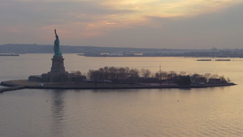 Flying by the Statue of Liberty and Liberty Island in New York, winter, twilight Aerial Stock Footage | AX65_0184