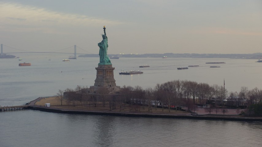 5K stock footage aerial video of flying around the back of the Statue of Liberty and Liberty Island in New York, winter, twilight Aerial Stock Footage | AX65_0185