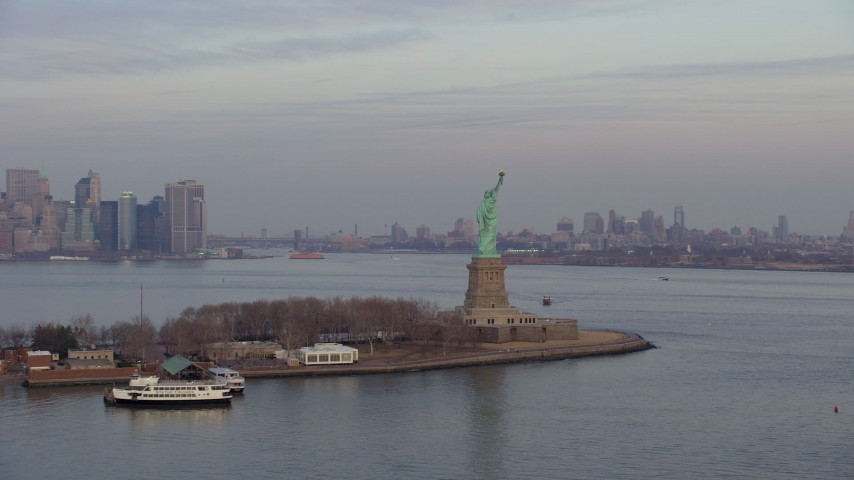 5K stock footage aerial video pass by the Statue of Liberty monument on Liberty Island with Lower Manhattan skyline in the background in New York, winter, twilight Aerial Stock Footage | AX65_0187