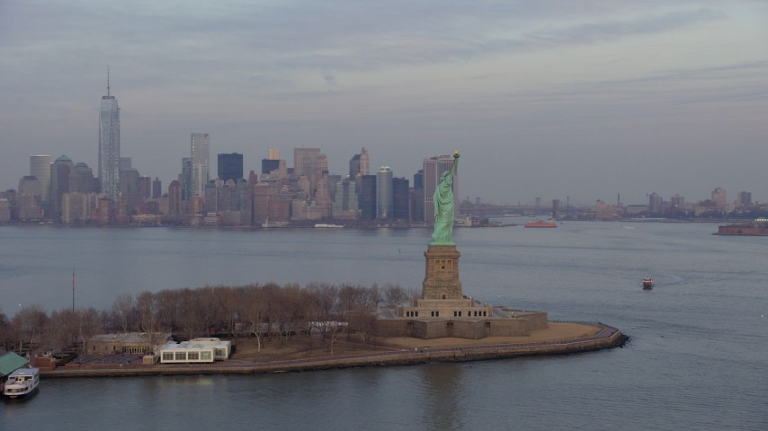 Flyby by the Statue of Liberty monument on Liberty Island with Lower Manhattan skyline in the background in New York, winter, twilight Aerial Stock Footage | AX65_0188