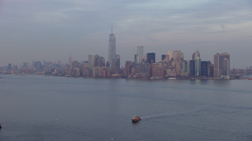 5K stock footage aerial video of Lower Manhattan skyline seen from New York Harbor, New York City, winter, twilight Aerial Stock Footage | AX65_0189