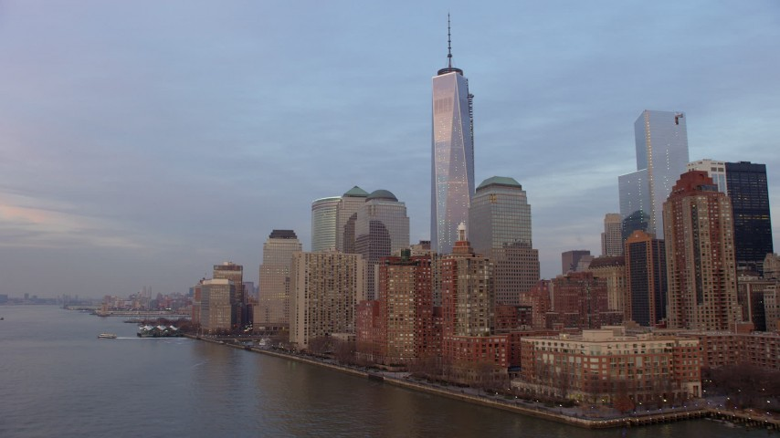 Fly low by riverfront high-rises around World Trade Center skyscrapers in New York City, winter, sunset Aerial Stock Footage | AX65_0193