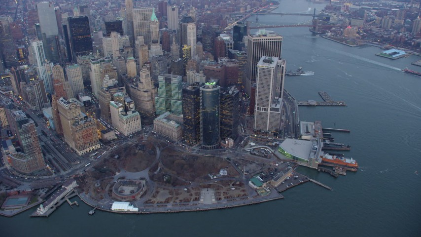 Pan and tilt from a bird's eye of Battery Park and Lower Manhattan skyscrapers, reveal Freedom Tower in New York City, winter, twilight Aerial Stock Footage | AX65_0215