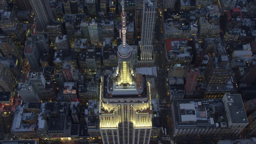 5K stock footage aerial video approach the Empire State Building in Midtown Manhattan, New York City, and tilt to a bird's eye view, winter, twilight Aerial Stock Footage | AX65_0236