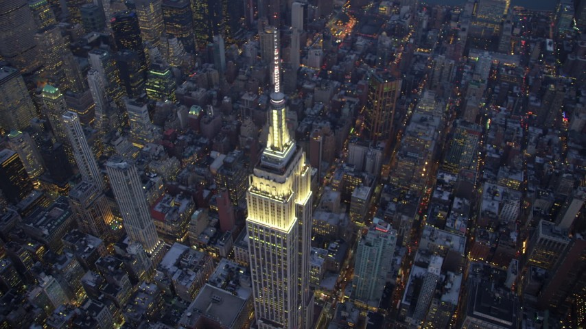 5K stock footage aerial video track top of the Empire State Building with gold lighting in Midtown Manhattan, New York City, winter, twilight Aerial Stock Footage | AX65_0246