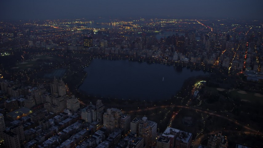5K stock footage aerial video pan across the reservoir and lights at Central Park in New York City, winter, night Aerial Stock Footage | AX65_0257