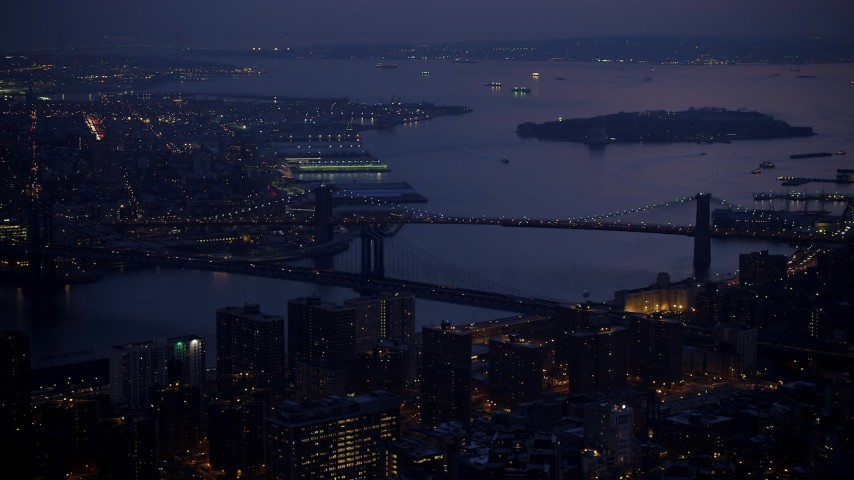 Manhattan and Brooklyn Bridges spanning East River, Governors Island in background, New York City, winter, twilight Aerial Stock Footage | AX65_0264