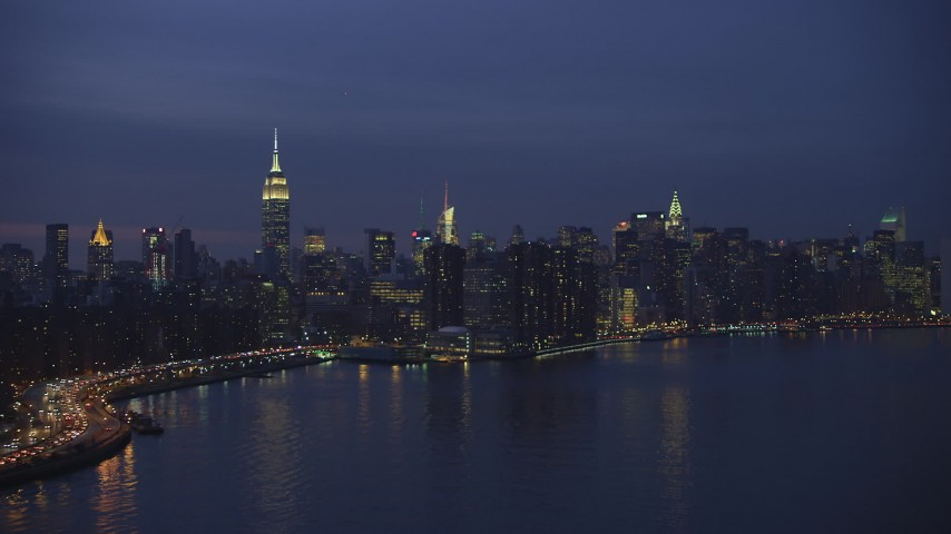 Approach waterfront condos with Empire State Building in background, Midtown Manhattan, New York City, winter, night Aerial Stock Footage | AX65_0267