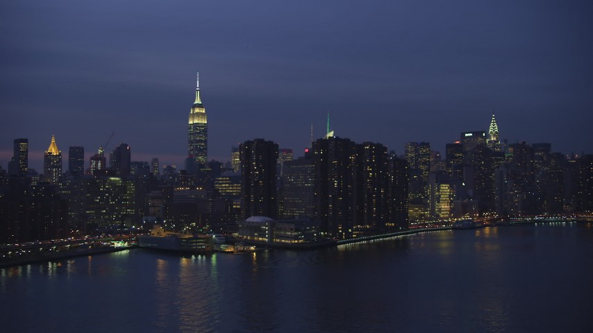 5K stock footage aerial video of passing riverfront condos with Empire State Building in background, Midtown Manhattan, New York City, winter, night Aerial Stock Footage   AX65_0268