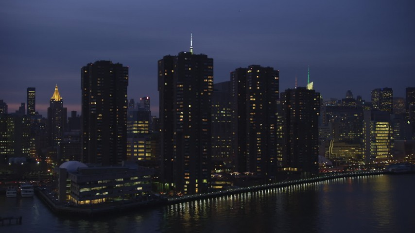 5K stock footage aerial video passing riverfront condos, NYU School of Medicine, Empire State Building in background, Midtown, NYC, winter, night Aerial Stock Footage | AX65_0269